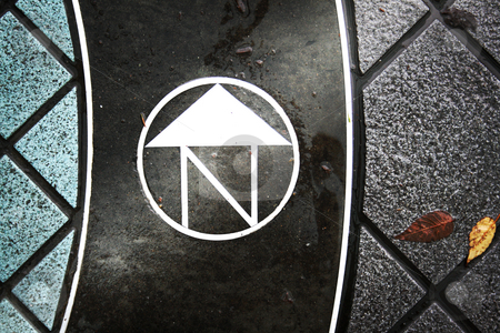 North stock photo, Sign marker embedded in a city sidewalk indicated which way is north. by Nathan Smith