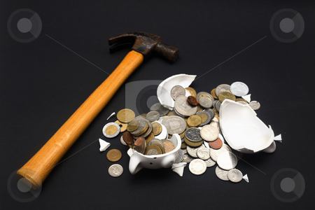 Broken Piggy Bank stock photo, A broken piggy bank isolated on a dark background with loads of coins from around the world and a hammer. by Daniel Wiedemann