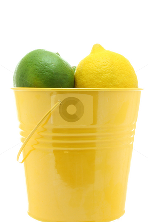 Bucket of citrus stock photo, Two limes and one lemon in a yellow bucket, isolated on white. by Jessica Tooley