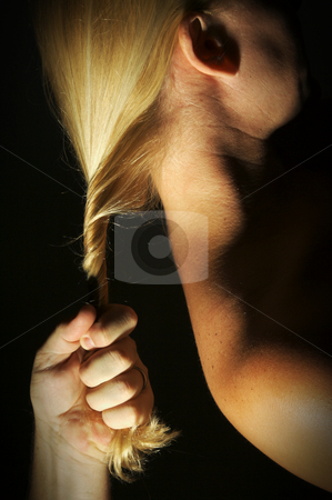 Hand pulling blonde hair stock photo, Abstract dramatically lit image of woman's shoulder, back and blond hair with male hand gripping her lock. by Andy Dean
