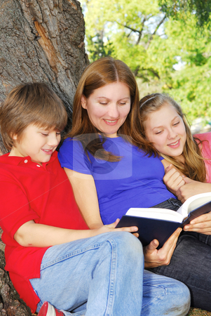 Family reading a book stock photo, Family of mother and children reading a book under a tree in summer park by Elena Elisseeva