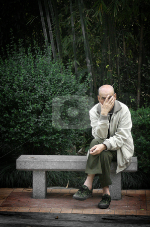 On a Bench stock photo, An elderly Chinese gentleman peeks through his fingers while sitting cross-legged on a stone bench. by Nathan Smith