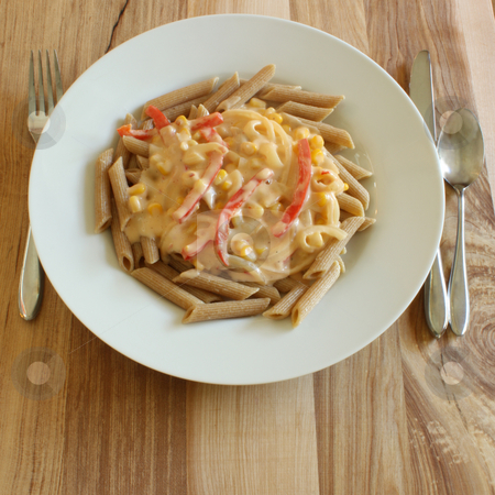 Pasta with White Vegetable Sauce stock photo, Whole wheat penne pasta, cooked and served with a vegetable white sauce, on a white plate upon a wooden table. by Jessica Tooley