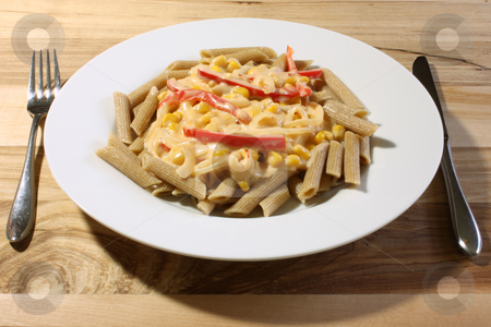 Cooked Pasta stock photo, Whole wheat penne pasta, cooked and served with a vegetable white sauce, on a white plate upon a wooden table. by Jessica Tooley