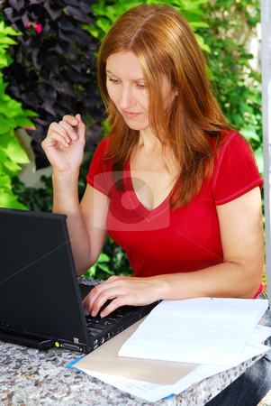 Woman working at home stock photo, Happy mature woman working on a portable computer in her garden by Elena Elisseeva