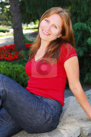 Mature woman relaxing stock photo, Smiling attractive mature woman relaxing in summer park by Elena Elisseeva