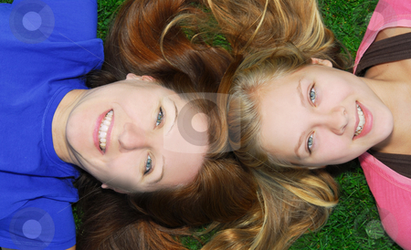Mother and daughter stock photo, Portrait of smiling family of mother and her teenage daughter lying on grass in summer park by Elena Elisseeva