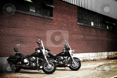 Dual Harleys stock photo, Two Harley-Davidson motorcycles parked outside a warehouse. by Nathan Smith