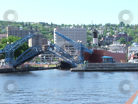Bridge opening in Duluth's Canal Park stock photo, A small divided bridge in Duluth's Canal Park opens to allow a small boat to enter the harbor leading to Lake Superior. by Dennis Thomsen