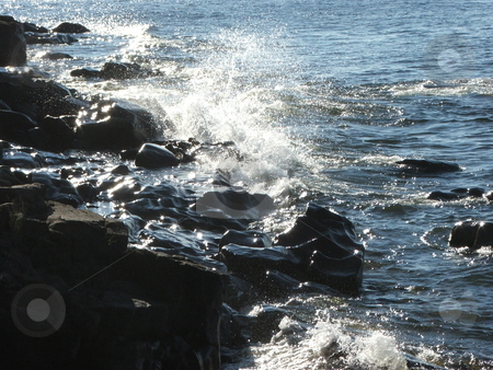 Small breakers on rocky shore stock photo, Waves break into the  rocky western shoreline of Lake Superior. by Dennis Thomsen