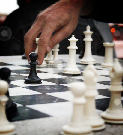 Chess on the Square stock photo, A man's hand about to move a chess piece with a black pawn in the foreground. by Nathan Smith