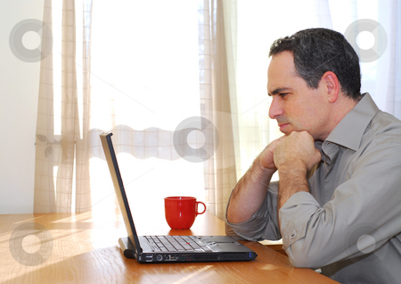 Man with laptop stock photo, Man sitting at his desk with a laptop looking concerned by Elena Elisseeva