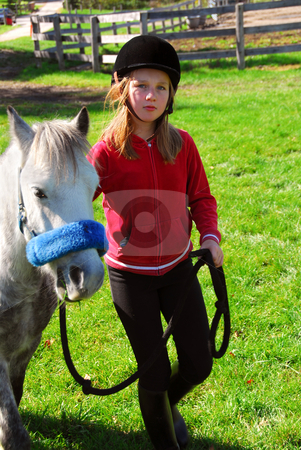Girl and pony stock photo, Young girl leading her pony out to pasture by Elena Elisseeva