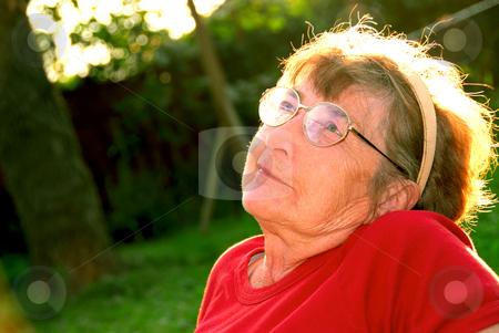 Elderly woman stock photo, Portrait of an elderly woman outside with backlit hair by Elena Elisseeva