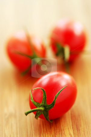 Small tomatoes stock photo, Small grape or cherry tomatoes on wooden cutting board by Elena Elisseeva