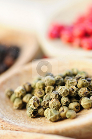 Assorted peppercorns stock photo, Assorted colorful peppercorns in wooden cooking spoons macro by Elena Elisseeva