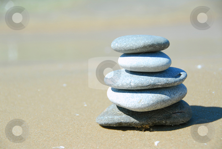 Stack rocks stock photo, Pebbles stacked on a sandy beach by Elena Elisseeva