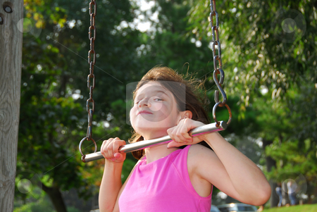 Girl on playground stock photo, Portrait of a young girl playing on a playground at summertime by Elena Elisseeva