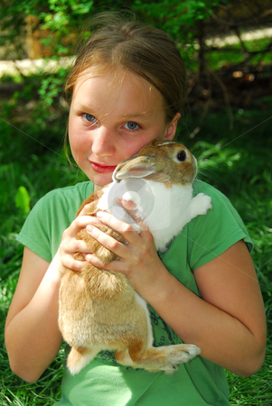 Gril with bunny stock photo, Portrait of a young girl holding a bunny outside by Elena Elisseeva