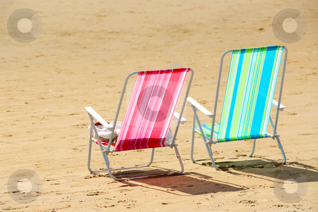 Beach chairs stock photo, Two empty colorful beach chairs on a sandy beach by Elena Elisseeva