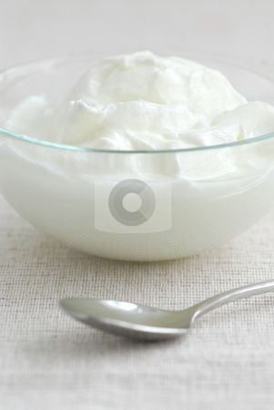 Yogurt and spoon stock photo, Fresh yogurt served in a clear glass bowl by Elena Elisseeva