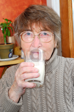 Woman glass milk stock photo, Elderly woman holding a glass of milk in her hand by Elena Elisseeva