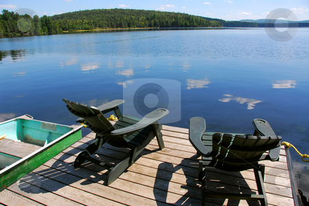 Chairs on dock stock photo, Two adirondack wooden chairs on dock facing a blue lake with clouds reflections by Elena Elisseeva