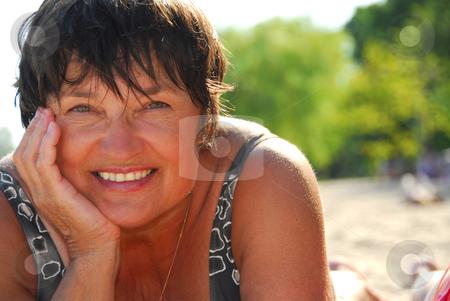 Mature woman beach stock photo, Portrait of a mature woman lying on a sandy beach by Elena Elisseeva