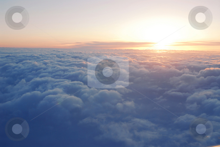 Above the clouds stock photo, Spectacular view of a sunset above the clouds from airplane window by Elena Elisseeva