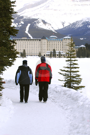 Lake Louise stock photo, A couple talking a walk in on scenic winter path at Chateau Lake Louise by Elena Elisseeva