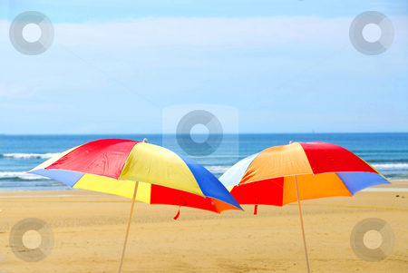 Beach umbrellas stock photo, Two beach ubrella standing on ocean shore by Elena Elisseeva