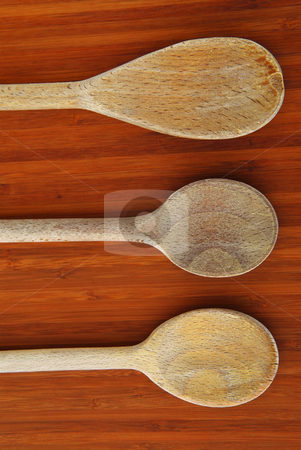Cooking spoons stock photo, Old wooden cooking spoons on a cutting board in a kitchen by Elena Elisseeva