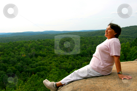 Woman enjoying scenery at cliff's edge stock photo, Mature woman sitting on cliff edge enjoying scenery by Elena Elisseeva