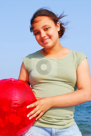 Young girl stock photo, Portrait of a beautiful young girl on sea shore with red beach ball by Elena Elisseeva