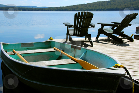 Chairs boat dock stock photo, Paddle boat and two adirondack wooden chairs on dock facing a blue lake by Elena Elisseeva