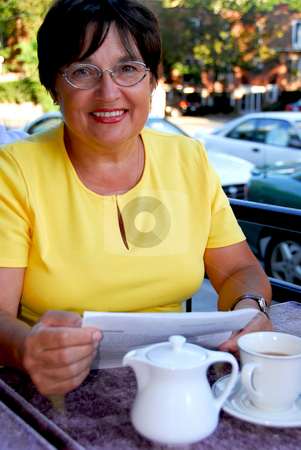 Mature woman reading stock photo, Mature woman reading papers in outdoor cafe by Elena Elisseeva