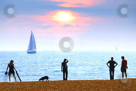Beach sunset stock photo, People on a beach watching scenic sunset by Elena Elisseeva