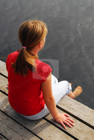 Girl child dock stock photo, Young girl dipping feet in the lake from a wooden boat dock by Elena Elisseeva
