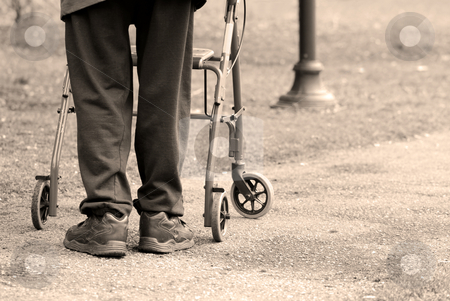 Old age stock photo, Senior man taking a walk in a park with the aid of a walking frame by Elena Elisseeva
