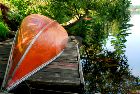 Canoe lake stock photo, Canoe on wooden dock on a lake by Elena Elisseeva