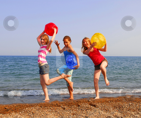 Girls on a beach stock photo, Three girls on a sandy beach being silly with colorful balls by Elena Elisseeva