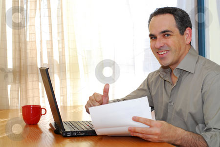 Man with laptop stock photo, Man sitting at a desk looking at bills and smiling by Elena Elisseeva
