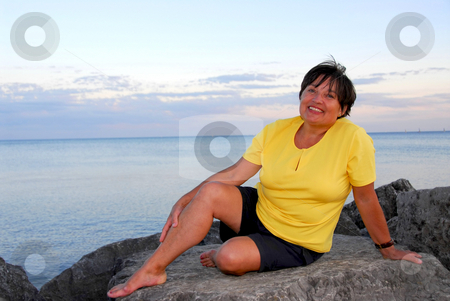 Mature woman relaxing stock photo, Mature woman relaxing on a shore by Elena Elisseeva