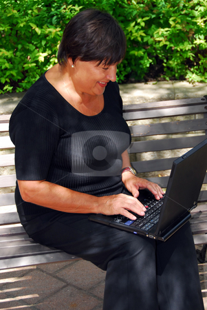 Mature woman computer stock photo, Mature woman typing on portable computer outdoor by Elena Elisseeva