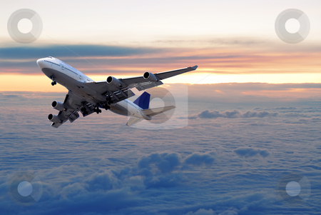 Above the clouds stock photo, Big passenger airplane flying above the clouds and sunset by Elena Elisseeva