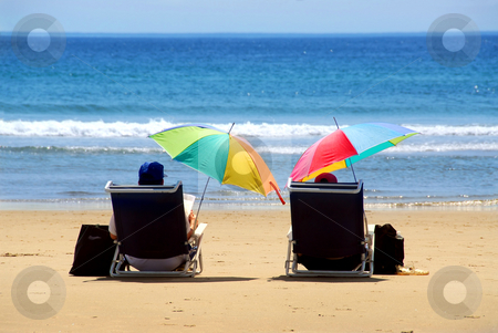 Couple beach stock photo, A couple relaxing on a beach under colorful umbrellas by Elena Elisseeva
