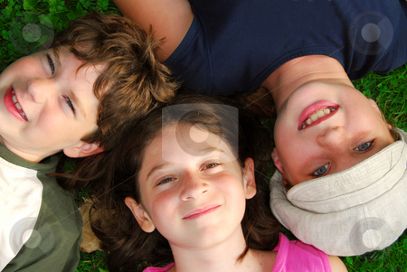 Kids stock photo, Portrait of three young children lying on grass looking up by Elena Elisseeva