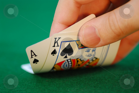 Gambling stock photo, Man's hand lifting up playing cards at a poker table by Elena Elisseeva
