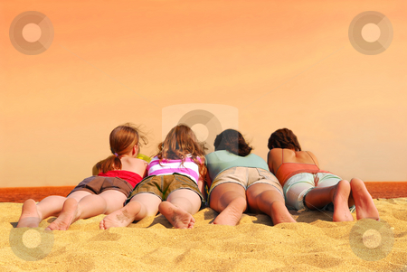 Four girls at orange sea stock photo, Four girls lying on a beach with orange sea and sky by Elena Elisseeva