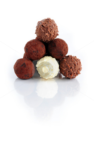 Chocolate truffles stock photo, Pyramid of assorted chocolate truffles on white background with reflection by Elena Elisseeva